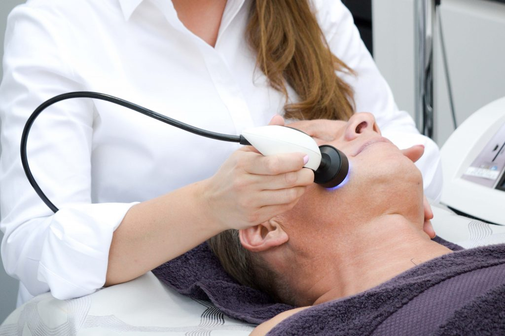 A man receiving a High-frequency treatment being performed by Ria Simpson at Darlings Faces